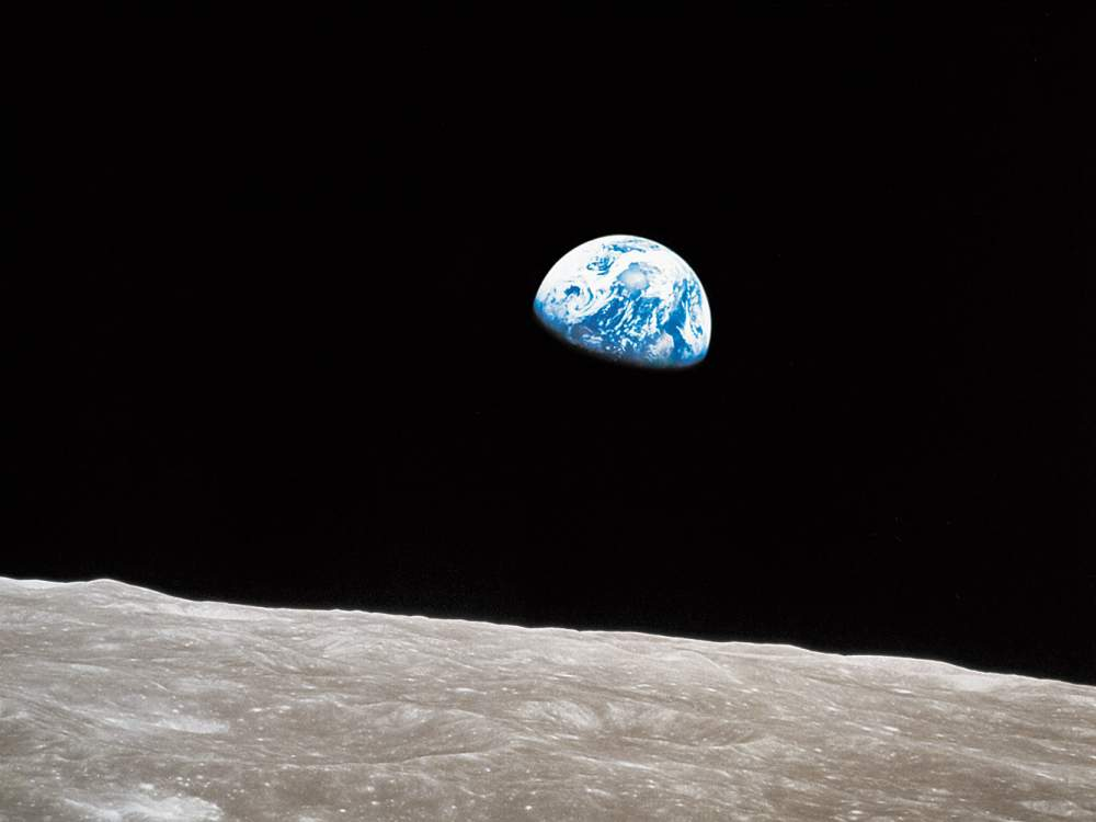 The view of earth rising over the moon's horizon