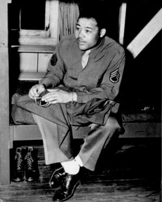 World Heavyweight champ Joseph Louis Barrow (aka Joe Louis) sews on the stripes of a technical sergeant — to which he has been promoted. April 10, 1945.  US Office of War Information.