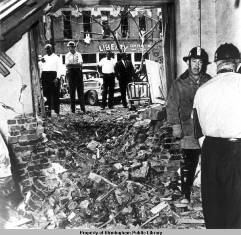 Photograph of debris after bombing with firemen on site